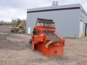A ScreenKing Mini soil screener being fed by a skidsteer loader